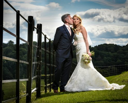 bride and groom near fence