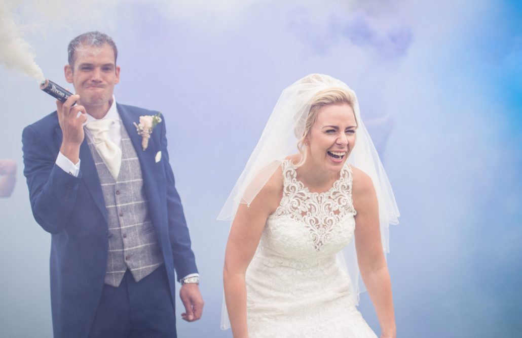 Bride and groom laughing whilst purple smoke bomb is going off