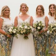 Bride and bridesmaid standing together with bouquets