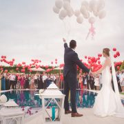 wedding guests with red balloons and the bride and groom
