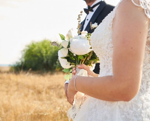 bride holding a bouquet of white peonies