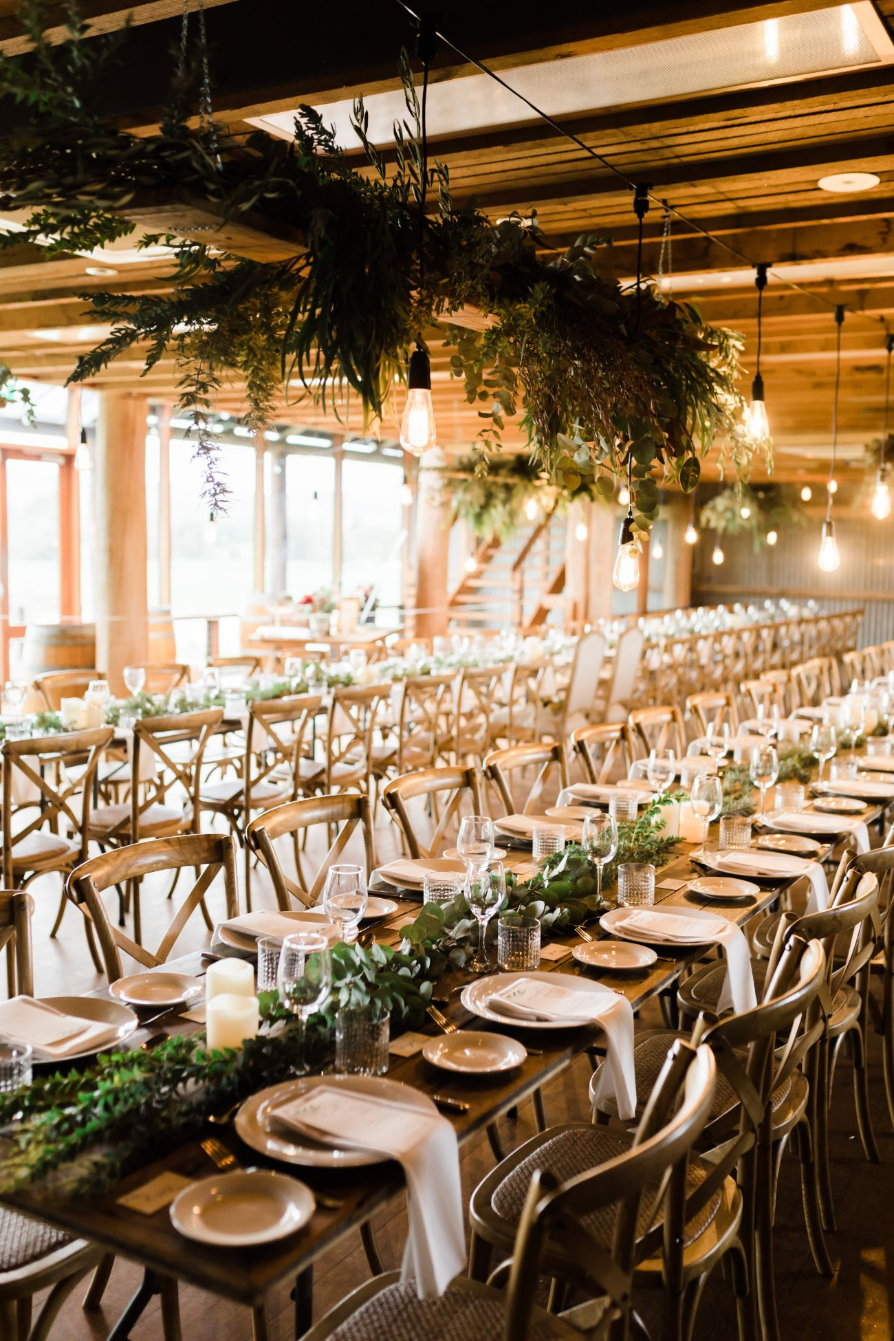 Wedding banquet tables decorated with a foliage runner