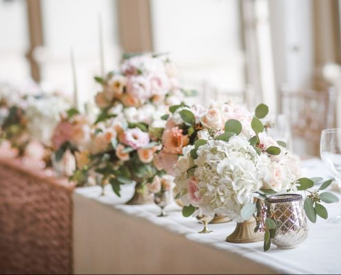Top wedding table with bridesmaids bouquet in vases with rose gold runner