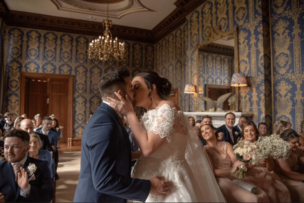 Bride and groom kiss during wedding ceremony at Soughton Hall
