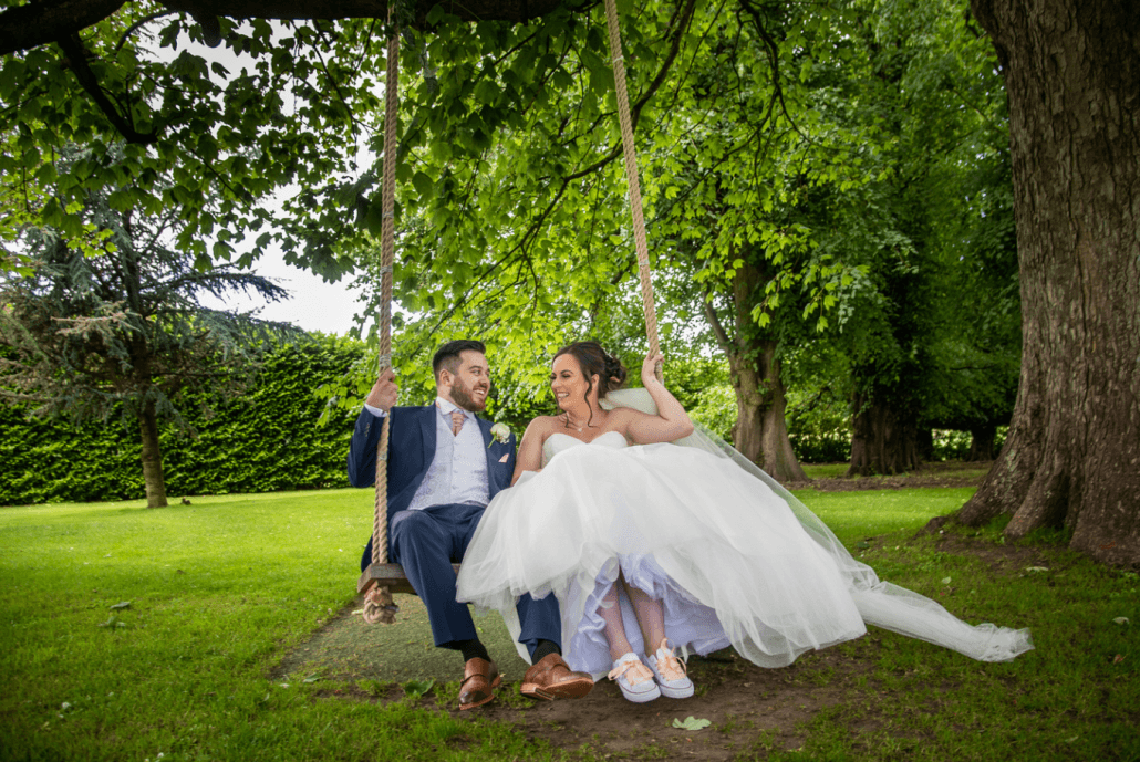Bride and groom playing on the swing at Soughton Hall