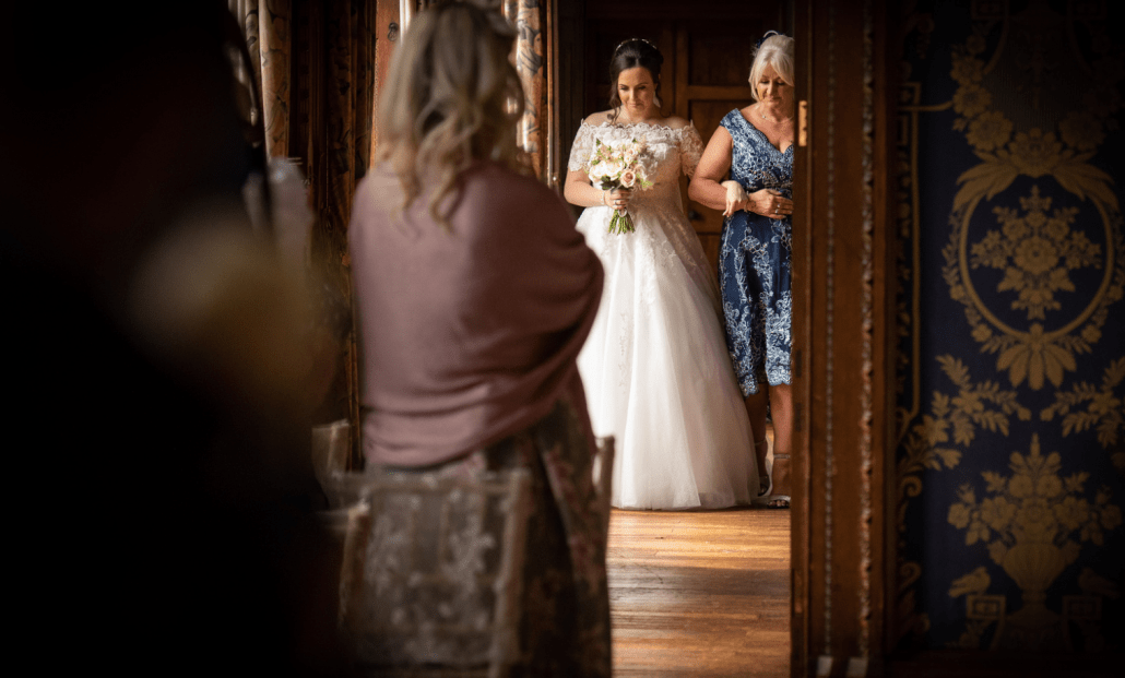 Mother walking bride down the aisle at Soughton Hall