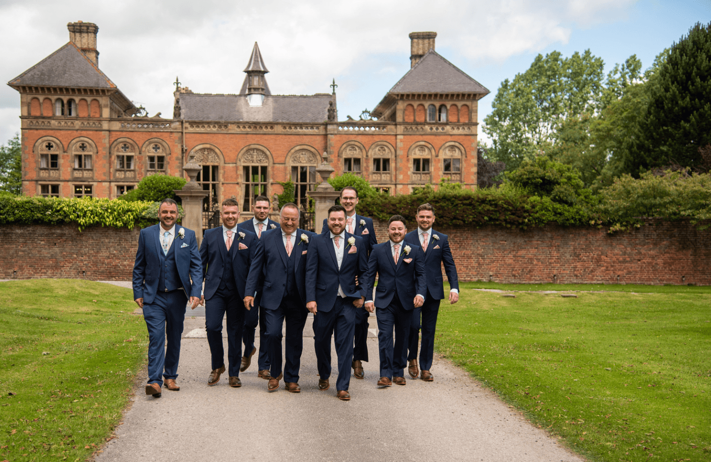Groomsmen walking outside Soughton Hall