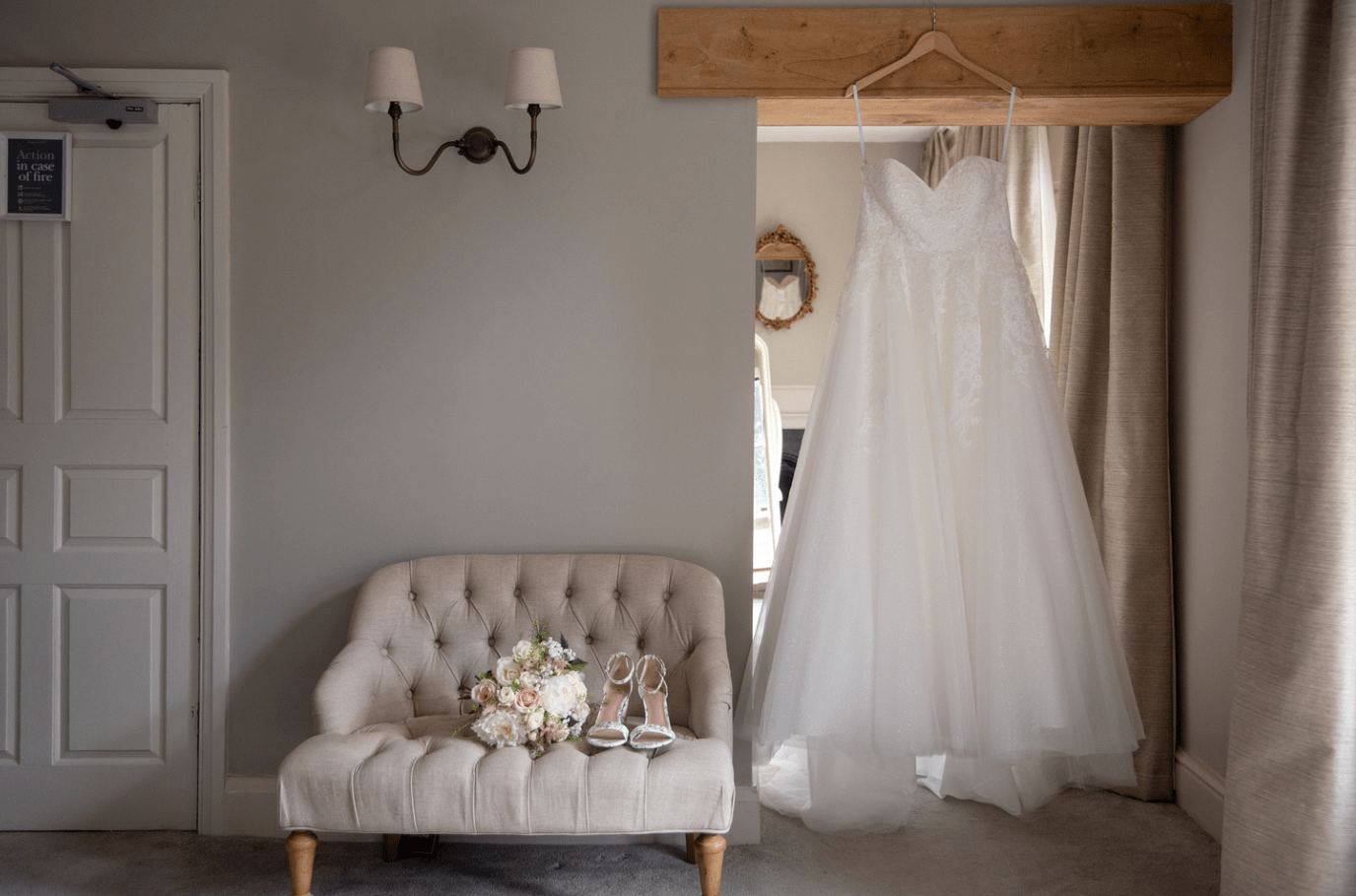 Wedding dress hanging on a door frame next to shoes and bouquet