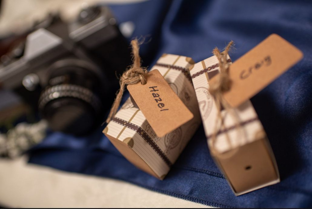 Bride and groom travel themed wedding with small suitcases as name cards