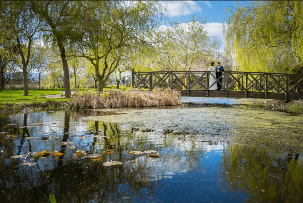 bride and groom standing on a bridge at North Wales venue