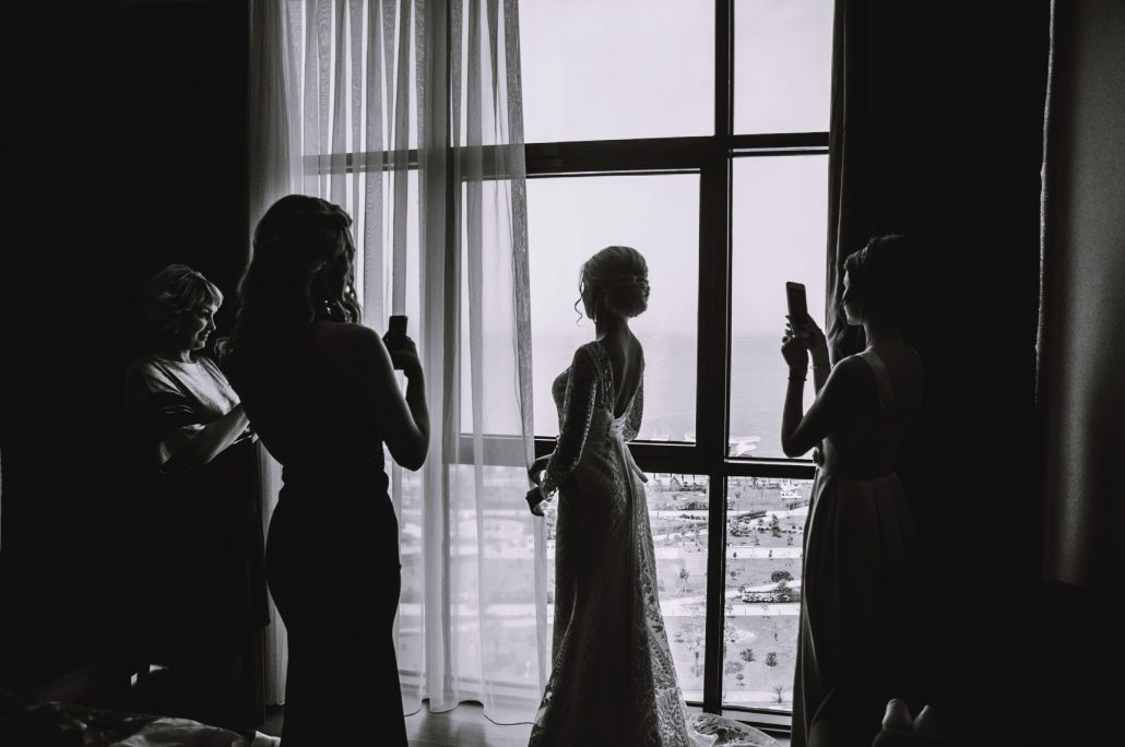 Bridesmaids taking a photo of the bride on her wedding day
