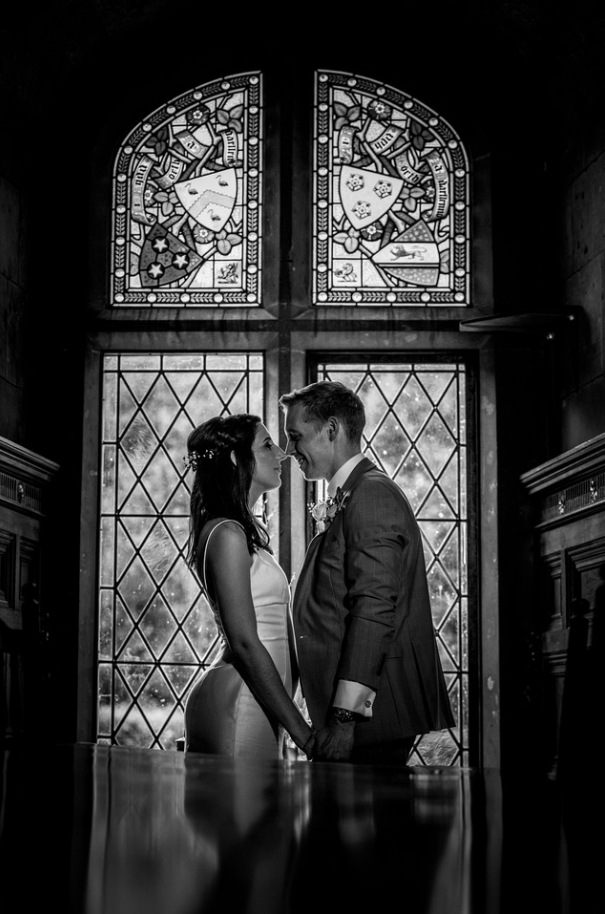 Bride and groom in front of a stained glass window at Tower wedding venue