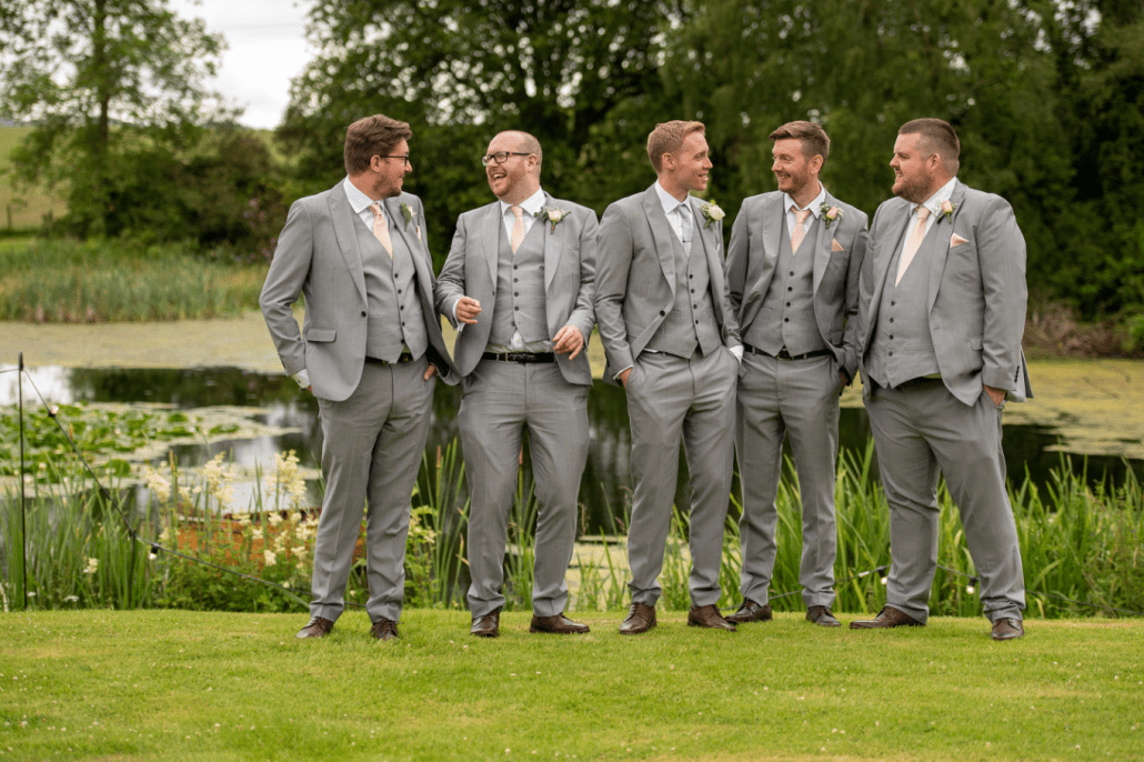 Groomsmen lined up in front of the pond at Tower