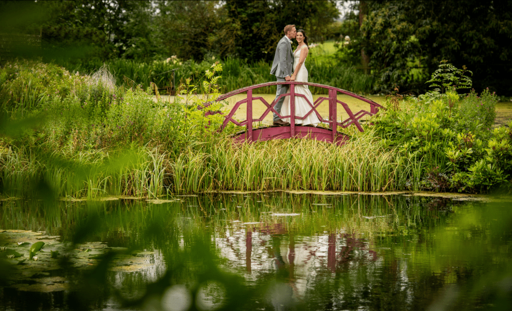 Bride and groom standing on a bridge over the pond at Tower, North Wales