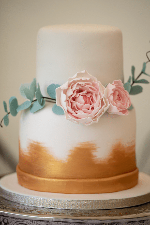 Wedding cake with pink flowers and green foliage icing