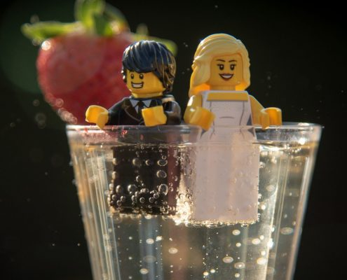 Lego wedding couple sitting in a glass of prosecco