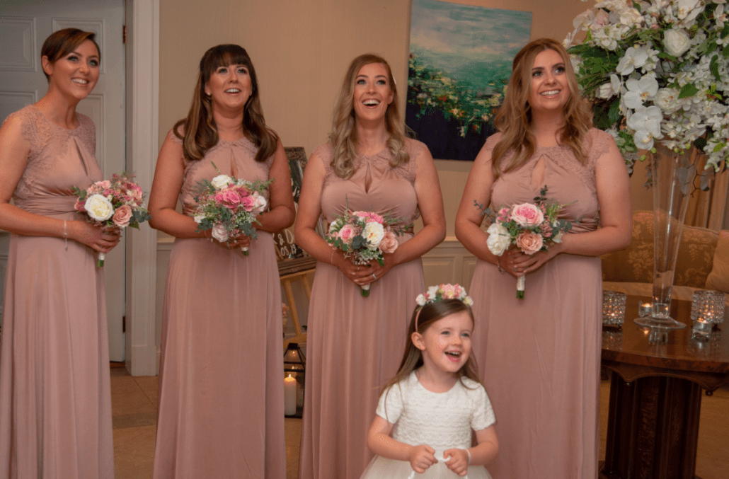 Bridesmaids watching the bride come down the stairs