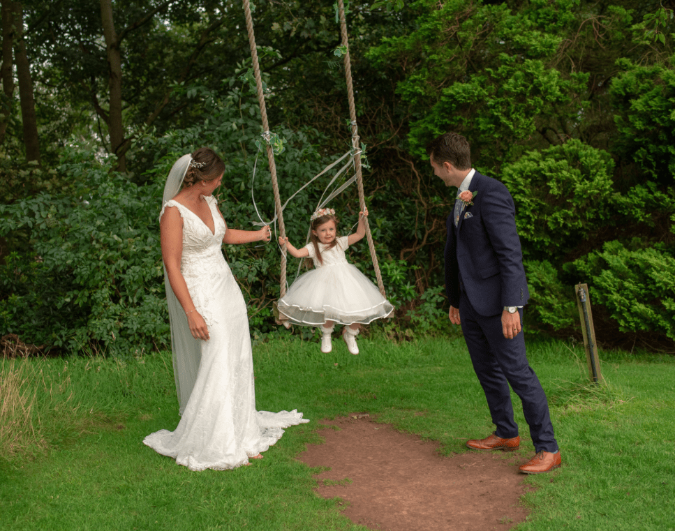 Bride and groom swinging their flower girl on a swing