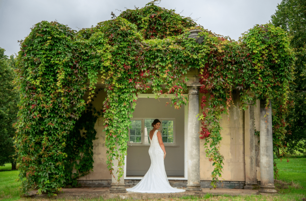 The bride standing under an arch of flowers