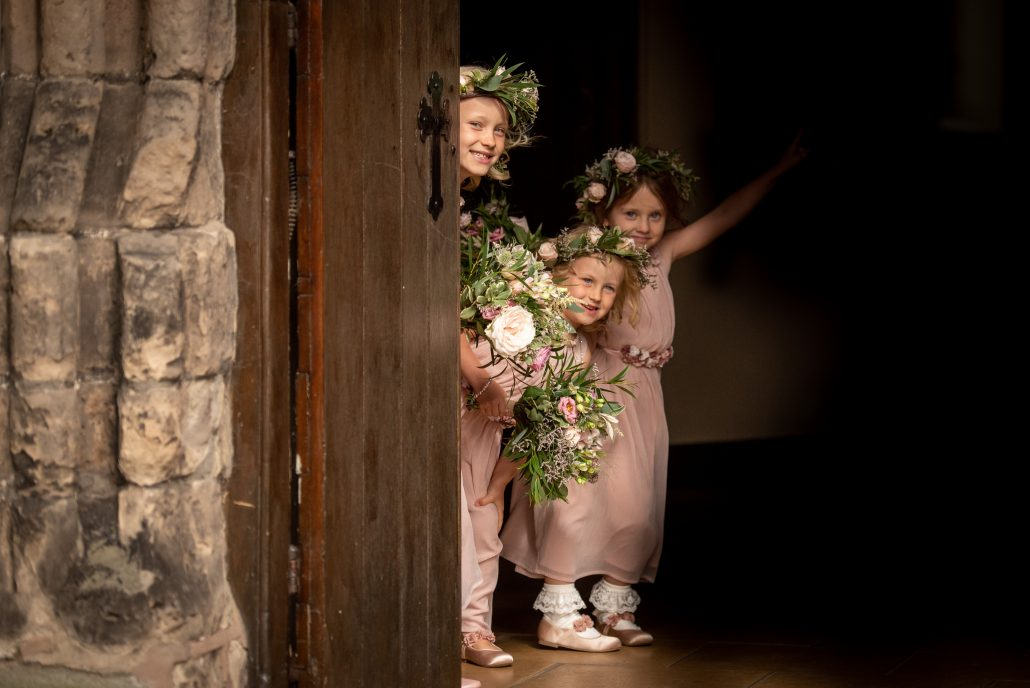 Flower girls peeking out from behind the large church door