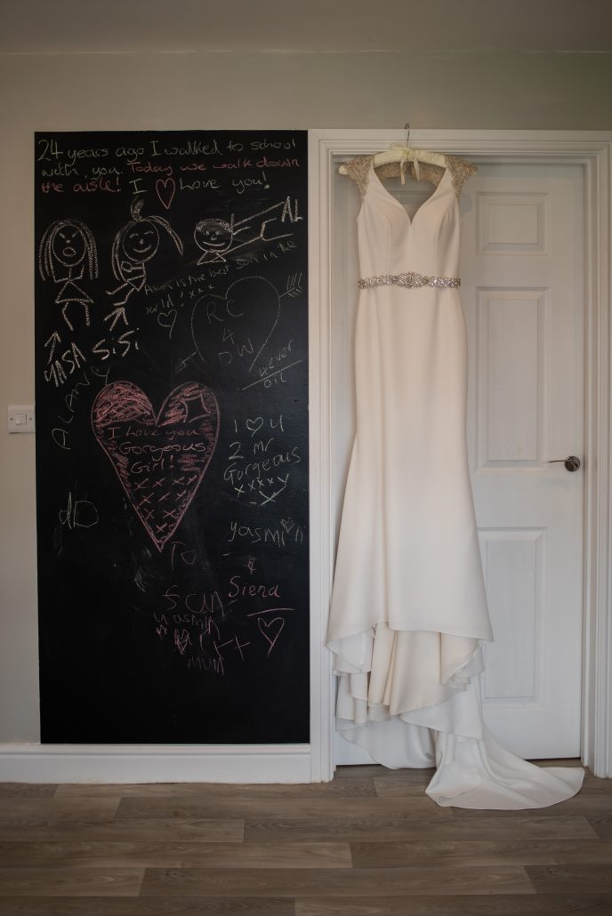 Bride's wedding dress hanging from a doorframe