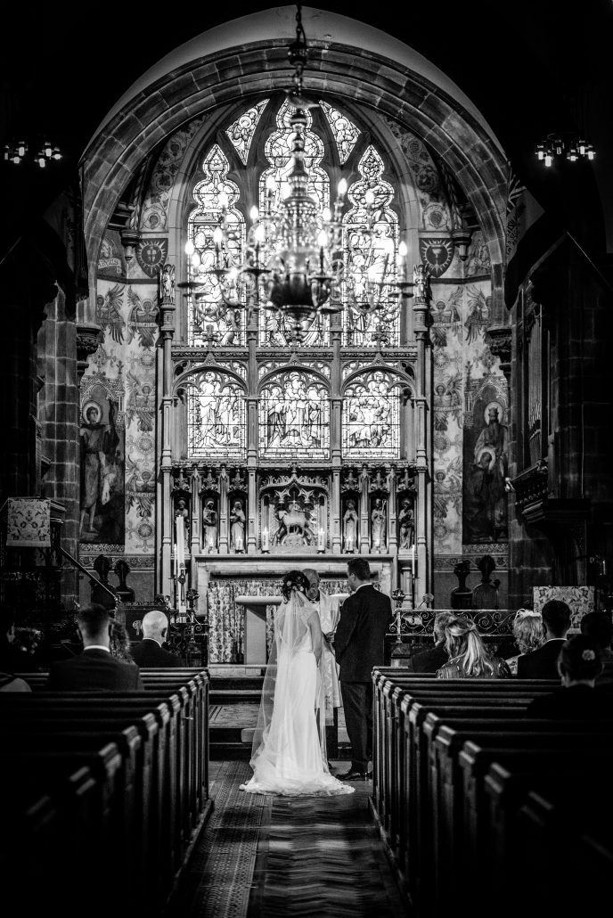 Gorgeous stained glass window in the church with the bride and groom in front of it