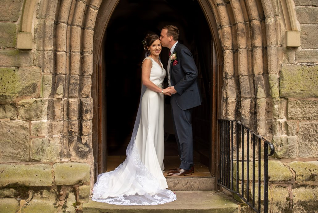 Bride and groom in the doorway of the church