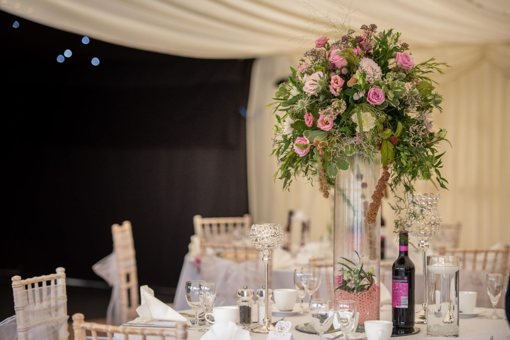Marquee with gorgeous wedding dressing and large flower centrepiece