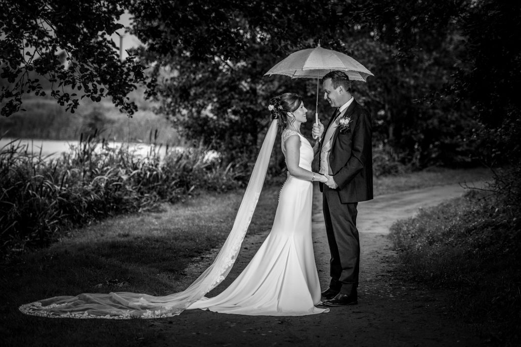 Bride and groom for Shropshire wedding under an umbrella