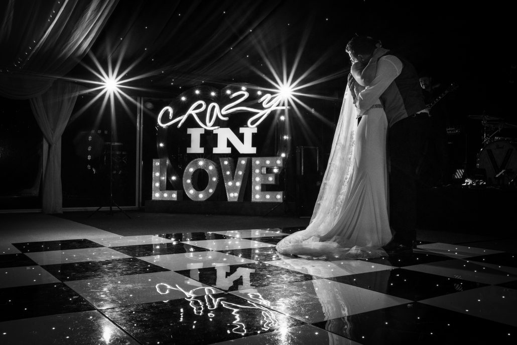 Bride and groom during their first dance with a 'Crazy in Love' sign in the background