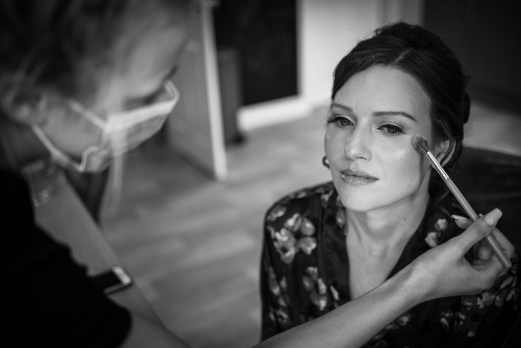 Bride having her make up down by a makeup artist wearing a mask