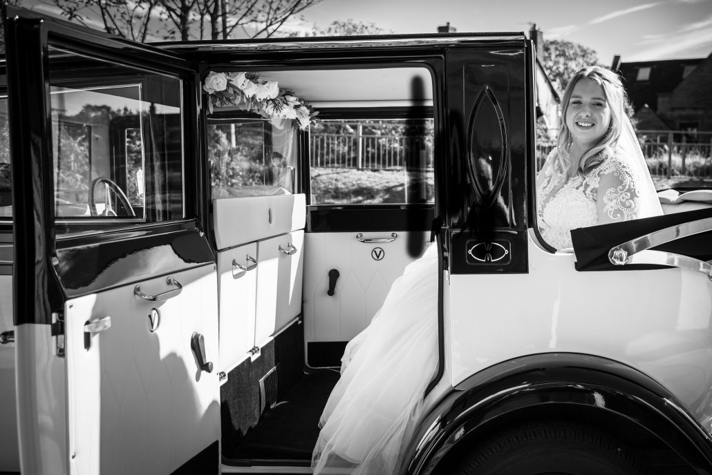 The bride in the back of the vintage car before getting married in Liverpool