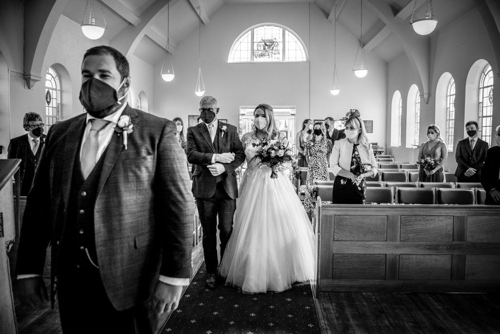 Bride and her father walking down the aisle while wearing masks