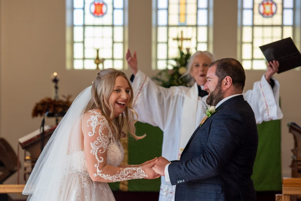 Couple laughing at the alter while getting married