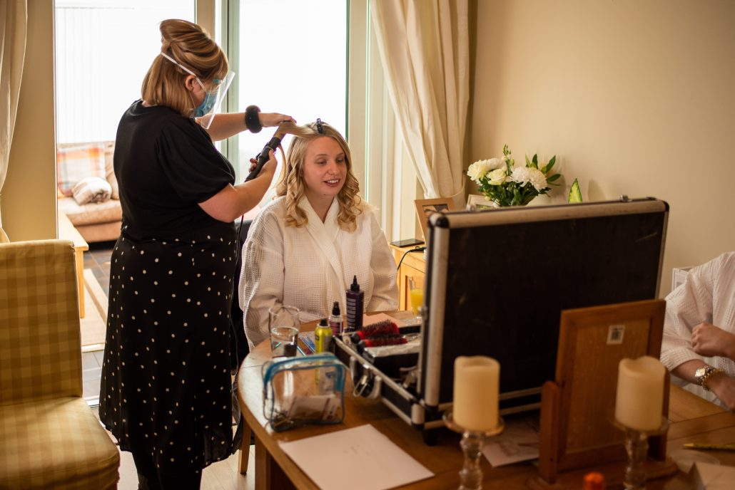 Bride getting ready at home while hairdresser does her hair