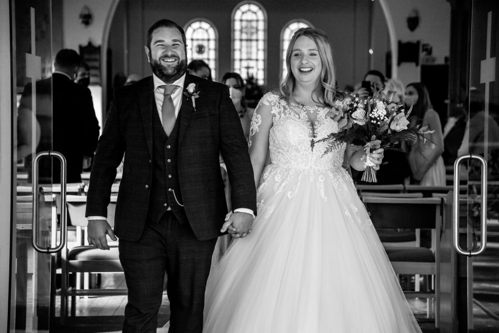 Husband and wife walking up the aisle after getting married