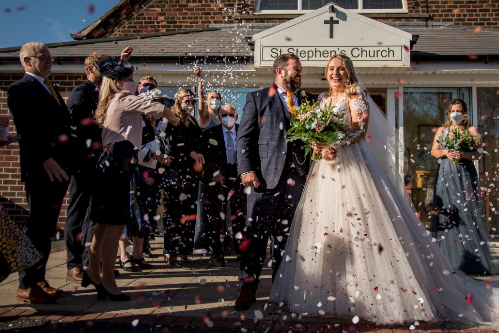 Bride and groom outside the church for a confetti shot