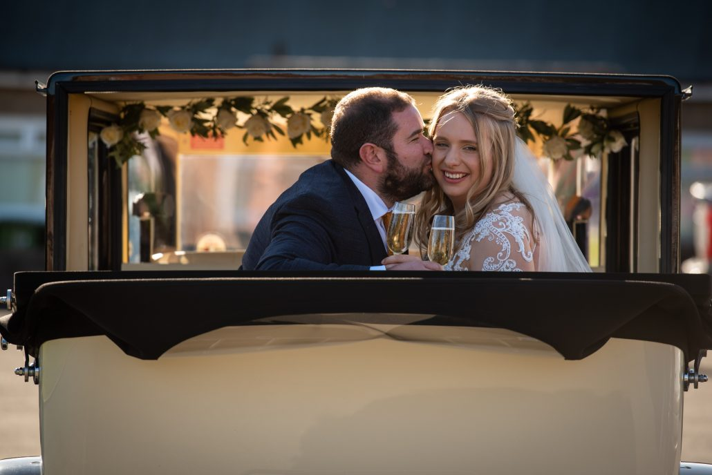 Bride and groom in the wedding car with some champagne