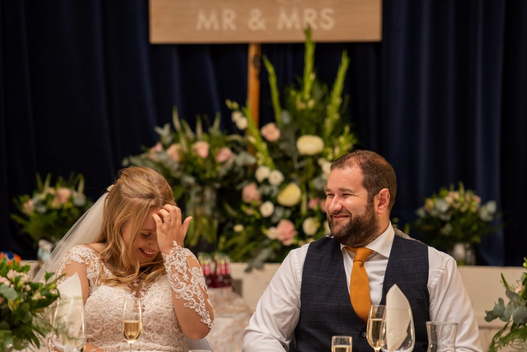 Bride and groom laughing during the wedding speeches