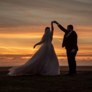 Couple dancing on the beach at sunset on their wedding day