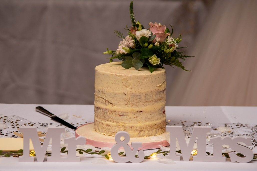 Simple buttercream wedding cake with real flowers
