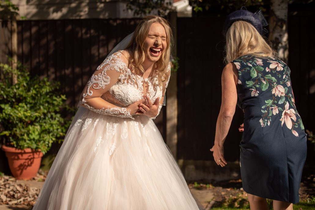 Bride and her mum laughing outside