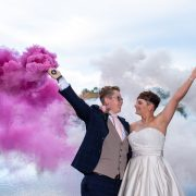 The bride and bride using coloured smoke bombs for their wedding photos