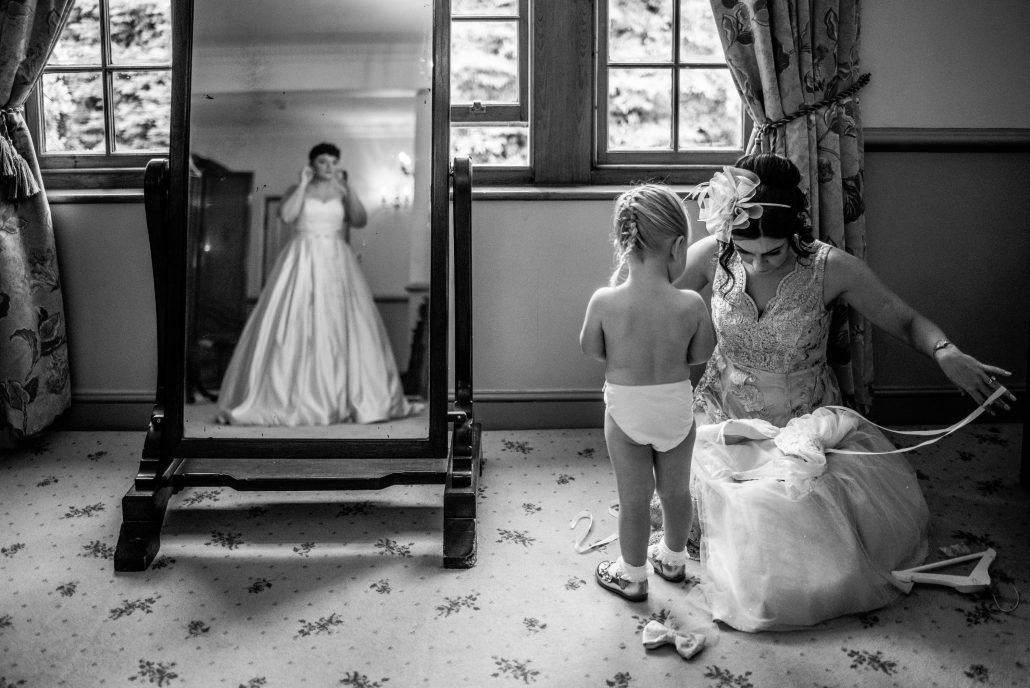 The bride looking in the mirror while her flower girl gets dressed